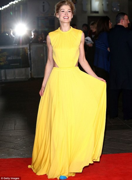 Rosamund Pike in long yellow gown from Alexander McQueen
